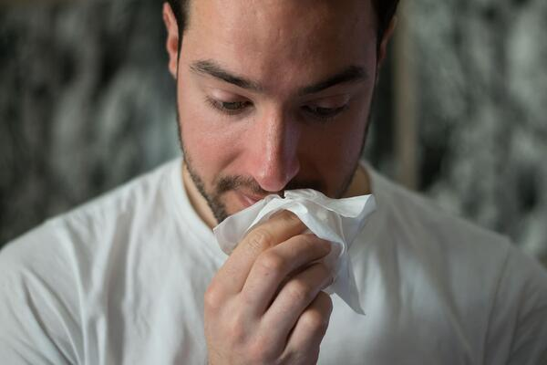 barbat care isi sufla nasul